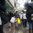 People with shopping bags walk in the rain on Oxford Street in central London on December 21, 2013 on the last weekend before Christmas. AFP PHOTO/JUSTIN TALLIS        (Photo credit should read JUSTIN TALLIS/AFP/Getty Images)