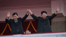 North Korea's leader Kim Jong-Un (R) and Chinese Politburo standing committee member Liu Yunshan (L) wave from a balcony towards participants of a mass military parade at Kim Il-Sung square in Pyongyang on October 10, 2015. North Korea was marking the 70th anniversary of its ruling Workers' Party. AFP PHOTO / Ed Jones        (Photo credit should read ED JONES/AFP/Getty Images)