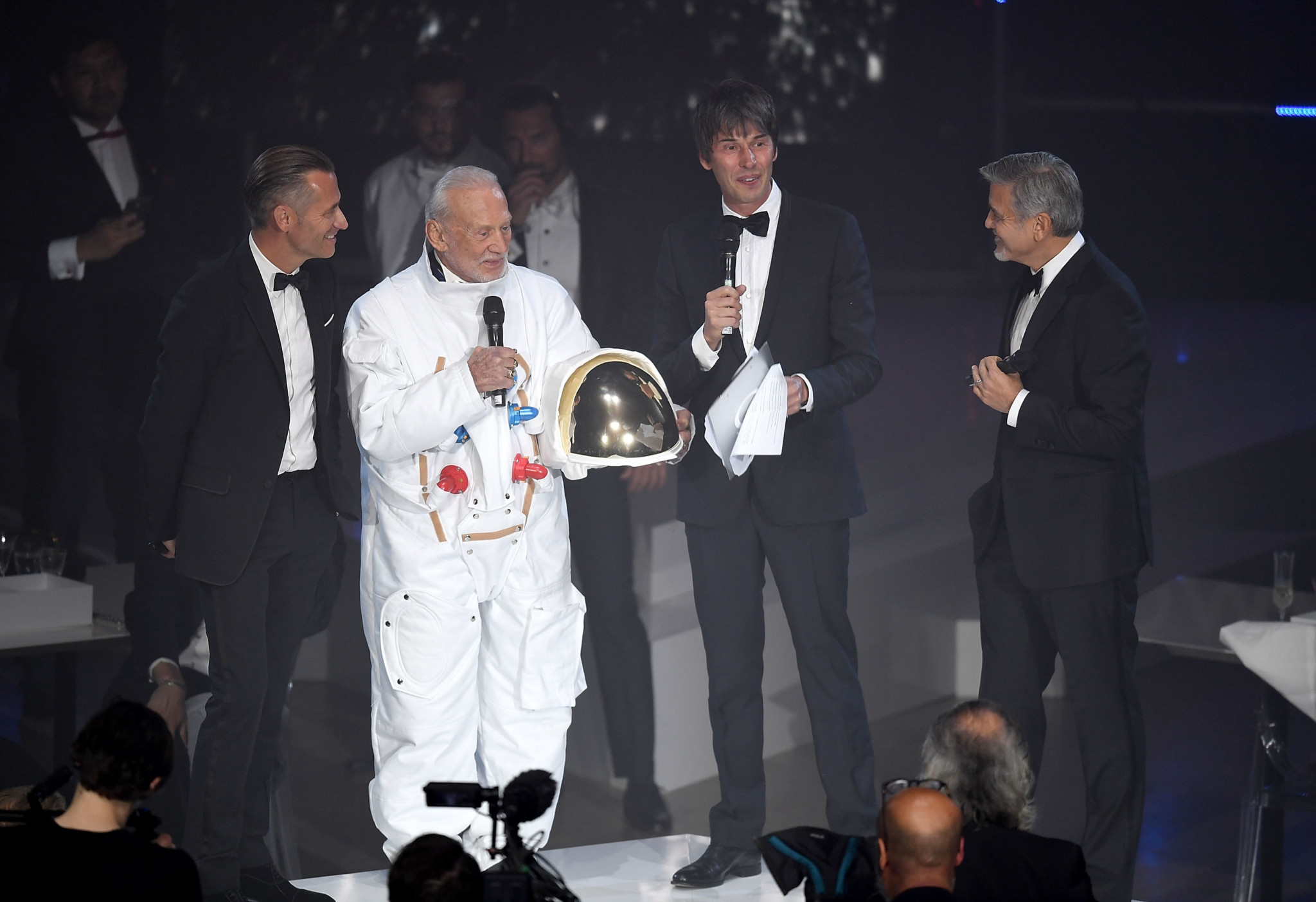 Omega President and CEO Raynald Aeschlimann, Buzz Aldrin, Prof. Brian Cox and George Clooney on stage at the OMEGA 'Lost In Space' dinner to celebrate the 60th anniversary of the OMEGA Speedmaster.