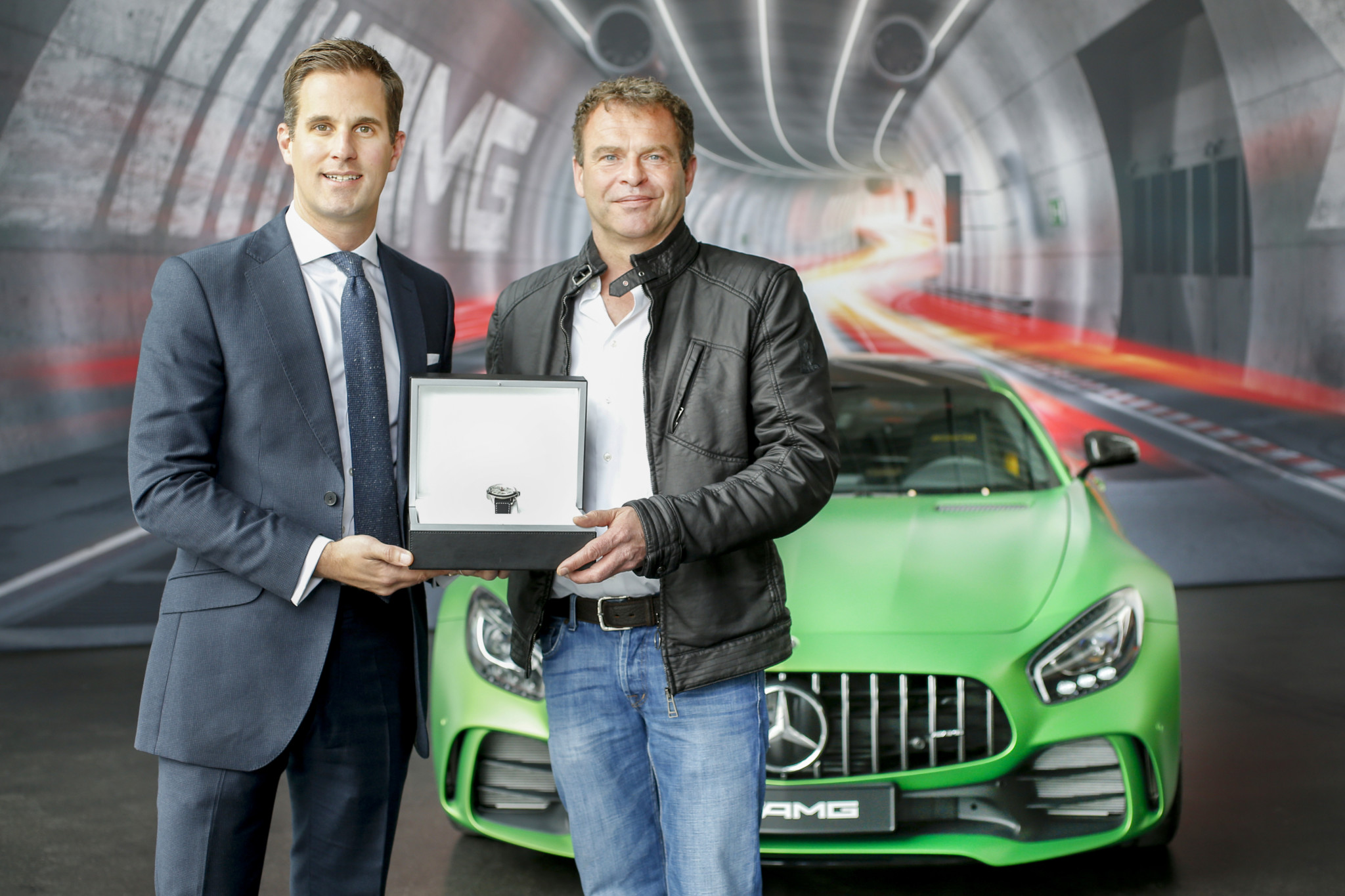 "IWC CEO Christoph Grainger-Herr visits the AMG manufacture in Affalterbach and hands over the Ingenieur Chronograph Sport Edition ""50th Anniversary of Mercedes-AMG"" to AMG CEO Tobias Moers."