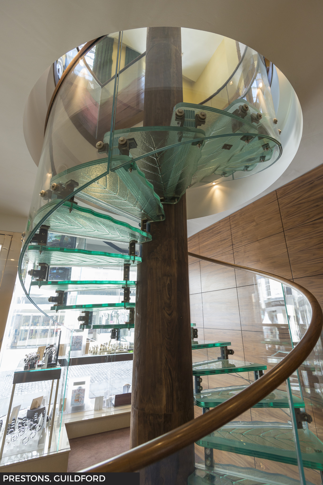 A striking spiral glass staircase connects the ground and first floors at Prestons in Guildford.
